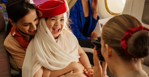Young Emirates passenger with cabin crew
